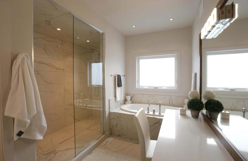 <p>The master bathroom features a glass-and-tile shower and an oval soaker tub. </p>