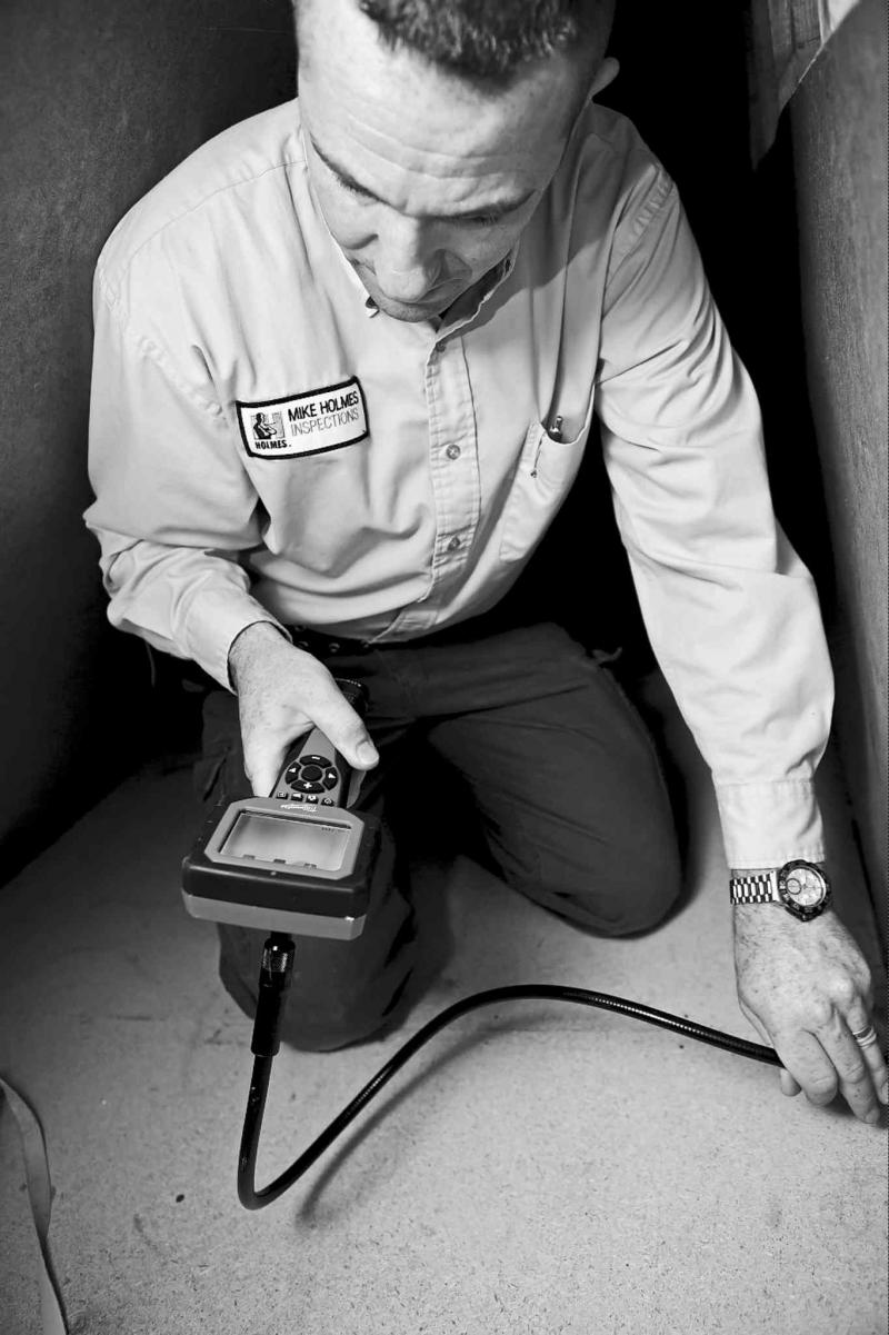 Inspecting the crawl space of a house with a digital inspection camera.
