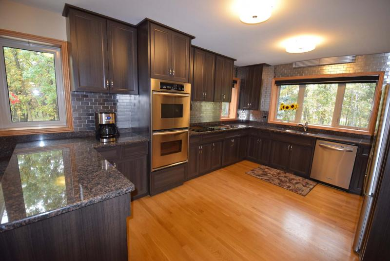 <p></p><p>The remodelled kitchen features a wealth of beautifully refaced cabinets, granite countertops, stainless tile backsplash, and forest views through huge windows.</p>