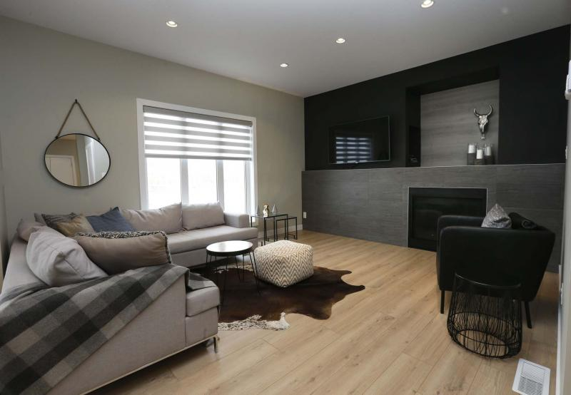 <p>WAYNE GLOWACKI / WINNIPEG FREE PRESS</p><p>The kitchen backs onto a spacious, yet intimate family room with medium brown oak-style luxury vinyl plank flooring and a grey tile entertainment unit with gas fireplace.</p></p>