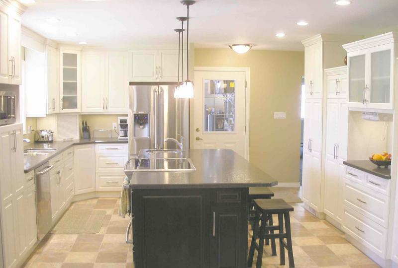 The remodelled kitchen features white painted maple cabinetry by pete