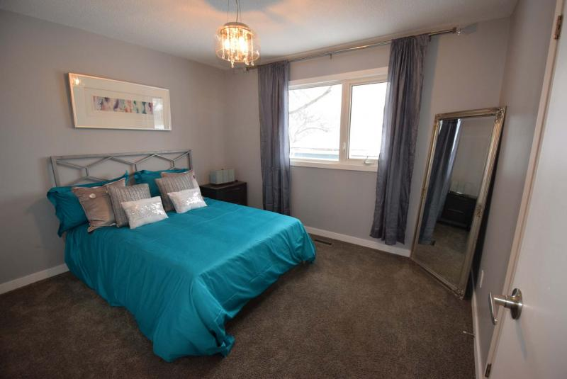 <p>Plush new carpeting and a warm grey colour palette give the master suite a cozy feel, while an oversized window lets in loads of natural light.</p>