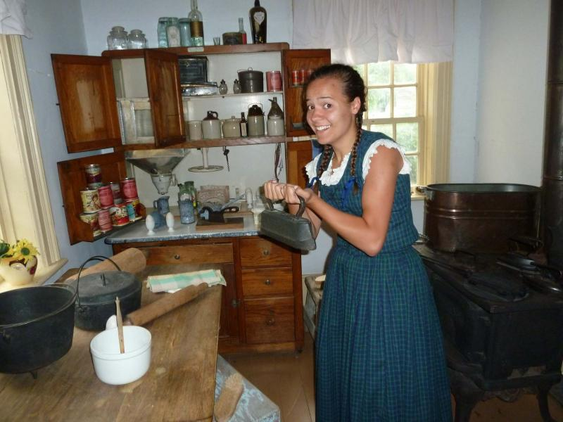 <p>Elisabeth, a summer employee at The Historical Museum of St. James / Assiniboia, with an antique iron.</p>