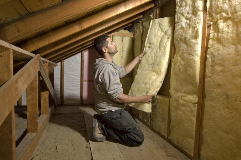 <p>SUPPLIED</p><p>A contractor installs batt insulation with the proper R-value for an attic space's walls. Insulation containing asbestos is usually safe as long as it's not disturbed.</p>