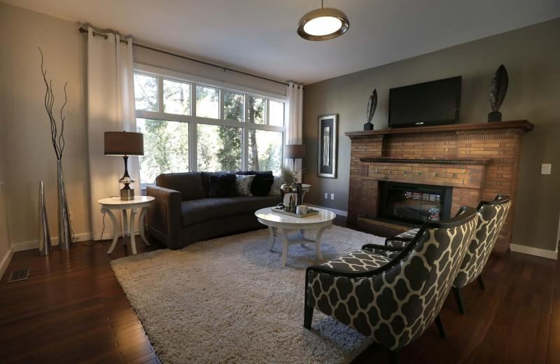<p>The living room in the main-floor condo has a large picture window and an electric brick fireplace</p>