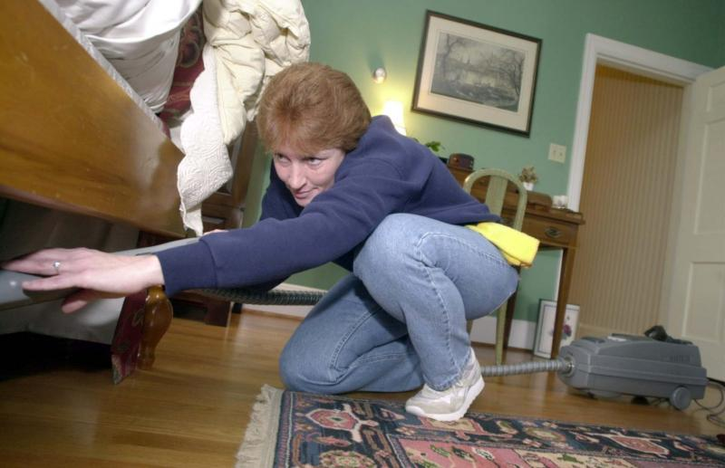 <p>David Perry / Lexington Herald-Leader</p><p>Deanna Raines, who works for the cleaning service A Touch of Class in Lexington, Kentucky, vacuums under a client's bed.</p>
