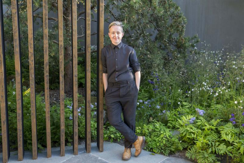 <p>MARIANNE MAJERUS</p><p>Landscape designer Charlotte Harris leans against the patinized copper verticals of the loggia she designed with woodland plantings on a rhythmic repeat framing the background.</p>