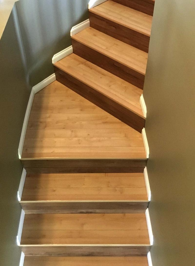 <p>Anne Hebert's stair treads in laminate with matching nosing, risers in a darker laminate, and white baseboards on every stair and landing.</p>