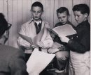 """Winnipeg Free Press Archives June 23, 1958 """"Let me hear how you'd read that line."""" John Hirsch, one of the directors of the Rainbow Stage, listens to three young aspirants for roles in The King And I. A notice of tryouts brought out a number of boys to fill the two important roles of the Young Prince and the son of Anna. Reading from left to right, these three aspirants are: Burton Cummings, 10, of 97 Lansdowne Ave; Fred Westman, 12, of 58 Crowson Bay; Jim McCarthy, 12, 263 Donalda Ave."""