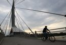 Cyclist rides over the Esplanade-Riel-pedestrian-bridge over the Red River Tuesday morning during a  seasonable cool morning- Standup photo– September 11, 2012   (JOE BRYKSA / WINNIPEG FREE PRESS)