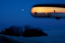 Brandon Sun 26032013 The rearview mirror reflects sunset to the west along Highway 10 near Minnedosa as an almost full moon rises to the east on Monday evening. (Tim Smith/Brandon Sun)