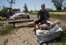Adam Dalman sits with some sandbags as he contemplates what he should do in the next week or so at Twin Lakes Beach. 140706 - Sunday, July 06, 2014 -  (MIKE DEAL / WINNIPEG FREE PRESS)