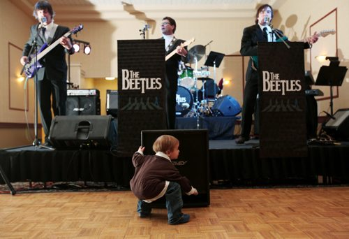 Brandon Sun 17032011 Three-year-old Mason Burgess puts his ear up to a speaker while listening to The Beetles perform at the Dance For Japan benefit social for Japan relief at the Victoria Inn Imperial Ballroom on Thursday evening. 100% of the proceeds from the event will be sent to the relief fund through the Canadian Red Cross. (Tim Smith/Brandon Sun)