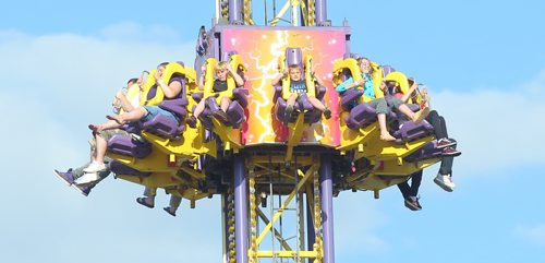 Brandon Sun Riders  grip their shoulder restrains as they fall earthbound on the Mega Drop ride in the midway at the Manitoba Summer Fair on Friday evening. (Bruce Bumstead/Brandon Sun)