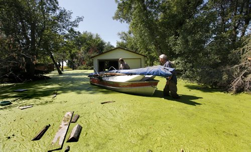 Albert Jacobs (hat) pushes his boat with help from his son Dave through stagnant water covered in green algae as they move personal belongings from Albert and his wife Elsie's home at 49 Twin Lakes Beach Rd. at Twin Beaches.  The couple in their 80's have been living in their home at the lake for over 25 years are now forced to leave it and rent a apartment in the city due to high water on Lake Manitoba seeping into their crawl space. Photo's of Twin Lakes Beaches. Saturday Special, Follow-up on Manitoba 2011 Flood by Melissa Martin. July 27, 2011 (RUTH BONNEVILLE / WINNIPEG FREE PRESS)