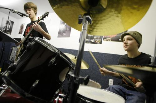 John Woods / Winnipeg Free Press / February  3 2007 - 070203  - Jared Kist (14) sings and plays guitar while Eric Brommell (14) plays drums in the rock band class at Spirit Music Saturday  Feb 3/07.