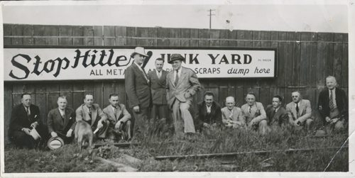 Winnipeg Free Press Archives Winnipeg Home Front  June 25, 1940  Situated at McPhillips Street and Higgins Avenue, this is one of three Stop-Hitler junkyards which are being opened by the Manitoba branch of the Canadian Automotive Wholesalers'  association in the province. The other two are situated in St. Boniface and Brandon. In the photograph taken Tuesday, are seen G.B. Stirriht, representing the department of munitions and supply, and  Mayor John Queen.