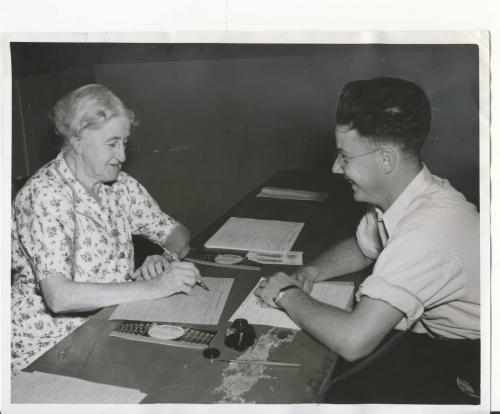 Winnipeg Free Press Archives WWII Home Front August 21, 1940. Canada's oldest Registrar Here is Mrs. Ida M. Brink, whose 81 years did not\ stop her from doing a full day's work for national registration. This picture was taken at General Wolfe school, where Mrs. Brink registered more than 100 persons, Monday. Her registrant in the picture is Gordon McNeil. fparchives