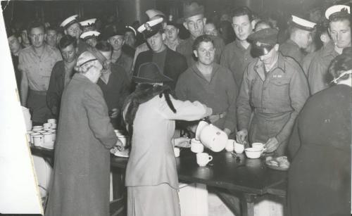 "Winnipeg Free Press Archives Winnipeg WWII Home Front  October 15, 1945 Winnipeg hospitality was again praised Saturday afternoon when hundreds of British repatriated prisoners of war from the Far East passed through the city over C.P.R lines en route to New York where they will catch a ship that will take them home. Seen at the left is Major William Holohan. of the Loyal, regiment who was captured at Singapore. He was greeted at the station by his brother, 82 | Harry Holohln (left). 488 Kylemore avenue who had ""ft seen him for 26 years The brothers, who are from Belfast, both served in the First Great War Some of the British repats are seen at the Bright, receiving refreshments from members of the reception committee."