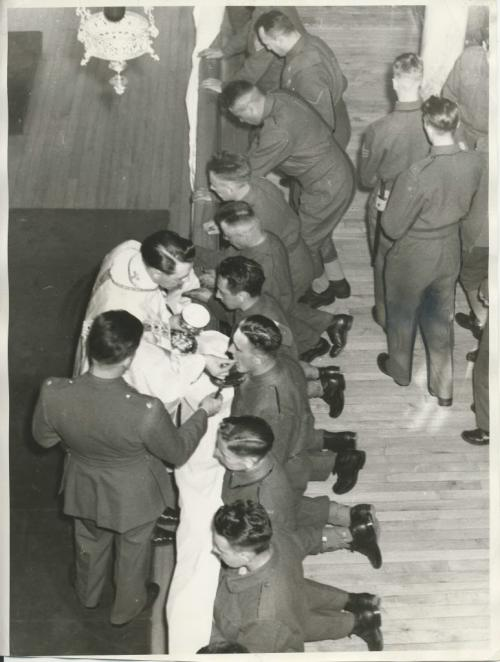 Winnipeg Free Press Archives Winnipeg WWII Home Front April 15, 1940 Soldiers Receive Communion About 250 Roman Catholic soldiers from Fort Osborne barracks attended mass Sunday morning in St. Joseph's Vocational school chapel. Following the mass, breakfast was served for the communicants. The breakfast, which was sponsored by the Knights of Columbus, was served by the Sisters, members of the Ladies' auxiliary of the school, and Amicus club girls. The picture shows the soldiers receiving communion.