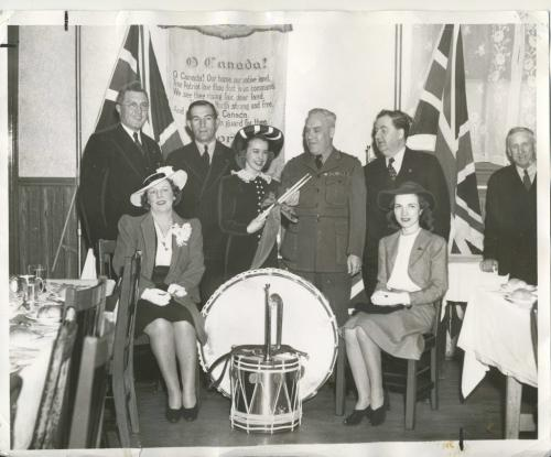 Winnipeg Free Press Archives Winnipeg WWII Home Front May 16, 1941 Drums For the Troops These bugles and drums will soon keep the beat in martial time for a unit of the Canadian army. They were presented to Military District No. 10 by the St. Boniface Kiwanis club at a luncheon, meeting, Thursday, at, the Nicolett  hotel. In the presentation pictured above are: Left to right, back row, Trafford Taylor, J. H. Mooradian, president of the club: Gladys Forrester, of the club's Thumbs Up revue; Lt.-Col. James Neish, who accepted the instruments presented by Mayor George MacLean, right. Front row, left to right, Dorothy Johnston and Ruth King, of the Thumbs Up revue.