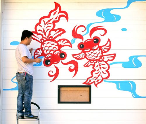 Brandon Sun Weidong Cong touches up a mural painted onto the door of his grocery store, Sunday afternoon on Rosser Avenue near Twelfth Street. Cong has opened the North China Supermarket, and commissioned a painting along the door as well as a side wall of his new business. (Colin Corneau/Brandon Sun)