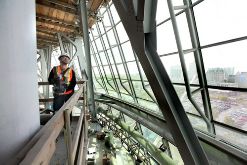 """A member of the media takes some shots from one of the viewing areas out into the  """"Cloud"""" -  a giant glass structure that surrounds the upper floors of the museum Wednesday morning. The steel skeleton visible beneath the museum's glasswork contains 5,400 tonnes of  steel, equivalent to the amount it would take to build 27 diesel electric locomotives.   Earlier building crews working on the Canadian Museum of Human Righs hoisted  the final piece of glass up to the chimney area of the Tower of Hope  which is 328 feet high on Wednesday morning. See Story Sept 20,  2012 (Ruth Bonneville/Winnipeg Free Press) CMHR"""