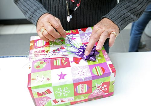 Brandon Sun 23122012 Volunteer Terry Gunnlaugson wraps a gift for a shopper at the CNIB gift wrapping station in the Shoppers Mall on Sunday. For a donation to the CNIB, shoppers can have their presents wrapped. All the supplies have been donated by mall businesses so every dollar donated is given to the CNIB. (Tim Smith/Brandon Sun)
