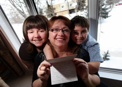 Trina Cimino, poses with her kids Kevin 8, and Sarah 11 holding a card from the School For the Deaf. Kids from the school across the road from her home helped out the family collecting donations after a holiday break in. Gabrielle's story. December 28, 2012 - (Phil Hossack / Winnipeg Free Press)