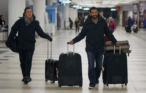 Toronto Blue Jays', Jose Bautista, right, pulls his luggage through at James Armstrong Richardson Airport, January 5, 2013. Winnipeg is one of the stops on the 3rd Annual Toronto Blue Jays Winter Tour. (TREVOR HAGAN/WINNIPEG FREE PRESS)
