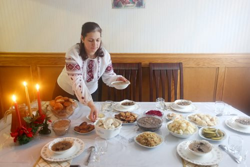 Brandon Sun 06012013 Nadiya Zaliska lays out food on the dinner table prior to Christmas Eve dinner at her family's home in Brandon on Sunday. For the many Ukrainians that follow the Julian calender today marks Christmas day. (Tim Smith/Brandon Sun)