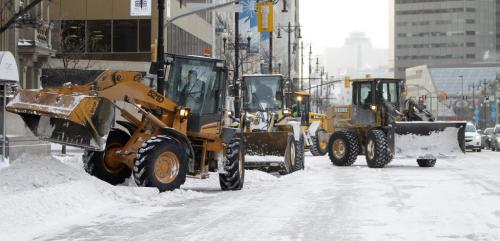 A team of loaders works to clear Main Street at McDermot Avenue, Saturday, January 12, 2013. (TREVOR HAGAN/WINNIPEG FREE PRESS)