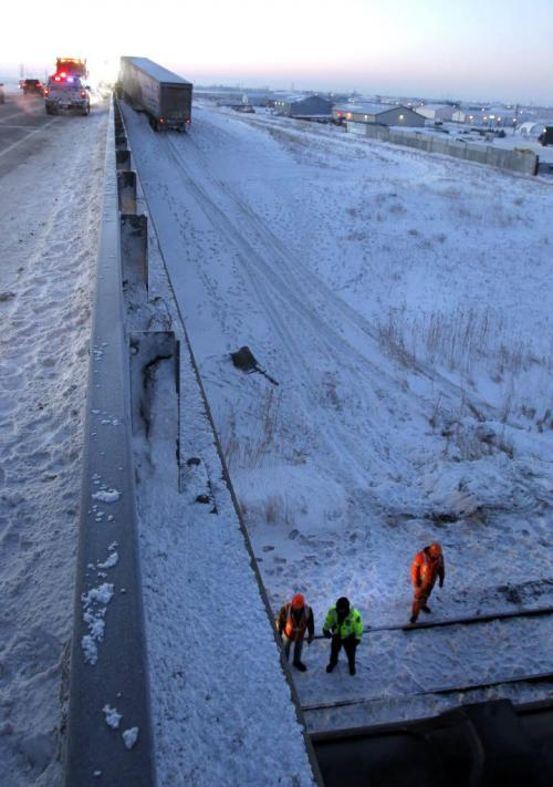 A semi-trailer is towed after it was heading southbound near Gunn Rd. and drove off the East Perimeter Highway Tuesday morning just prior to the rail overpass and continued down on to the rail tracks. A train struck the trailer.  (WAYNE GLOWACKI/WINNIPEG FREE PRESS) Winnipeg Free Press  Jan. 15 2013