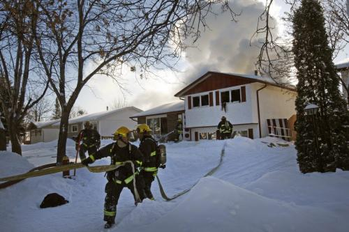 Fire heavily damaged a home at 54 Merrill Cres. near Antrim , there were no injuries ,the fire apparently started in upper level rear of the split level house around 12:45 pm - fire fighters rush to get extra hose to the homes front entrance and second floor  as fire raged at rear . KEN GIGLIOTTI / JAN. 25 2013 / WINNIPEG FREE PRESS