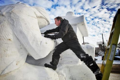 Dave Maddocks works on a Festival du Voyageur snow sculpture at Provencher Blvd and St. Joseph Street called The Piano Player Sunday afternoon.  130127 January 27, 2013 Mike Deal / Winnipeg Free Press