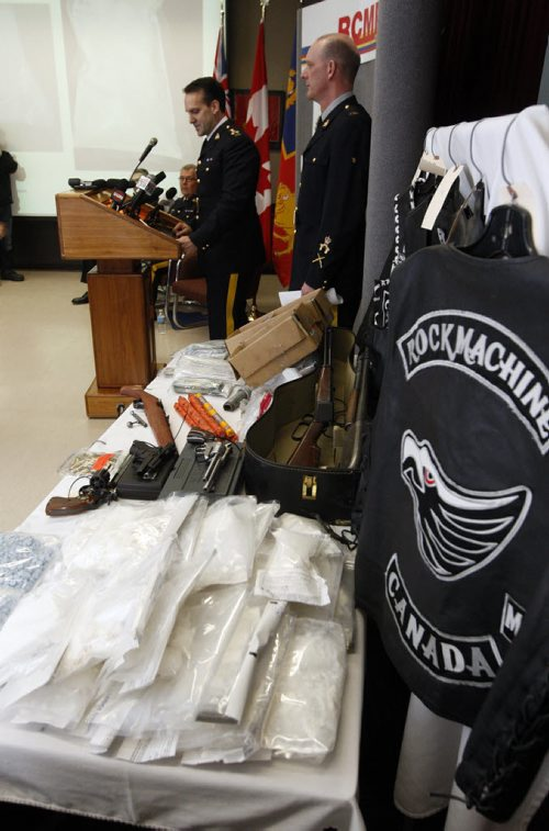 The RCMP announce a major take down called Operation Dilemma  involving 140 RCMP , targeting the  Rock Machine  Motorcycle Gang , 11 people were charged and drugs , guns and money seized in pic Assistant Director Kevin Brosseau  talks about the  operation with right Cpl Myles Hiebert beside him - cocc , GUNS  CLOTHING IN PIC  KEN GIGLIOTTI / JAN. 31 2013 / WINNIPEG FREE PRESS