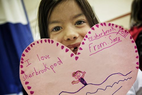 Sara Lewis, 6, holds up a valentine card she made while parents and neighbourhood residents discuss the issues surrounding the continued closure of the Sherbrook Pool several kids made valentines cards that will be put up on the side of the pool later this week.  130214 February 14, 2013 Mike Deal / Winnipeg Free Press