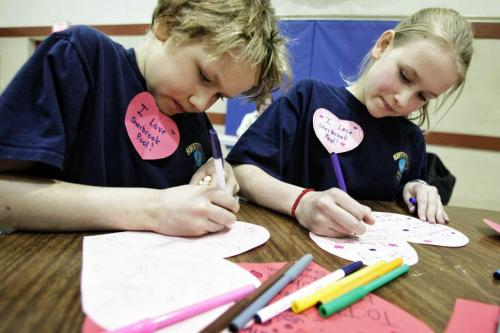 Aiden Dueck Thiessen, 9, and his sister Jubilee (right), 12, finish up valentine cards they made while parents and neighbourhood residents discuss the issues surrounding the continued closure of the Sherbrook Pool several kids made valentines cards that will be put up on the side of the pool later this week.  130214 February 14, 2013 Mike Deal / Winnipeg Free Press