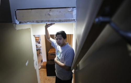 Arnel Mercado lives in a Pritchard Avenue home (695 Pritchard) that was built with falsified engineering seals, which the city is now investigating. Mercado said the city did not discover the problem until he applied for a permit to renovate his basement in November. Arnel is in the stairway to the basement where the Inspector found the headroom for the  stairs too low to meet code. He is holding a support beam. Jen Skerritt  story    (WAYNE GLOWACKI/WINNIPEG FREE PRESS) Feb. 19 2013