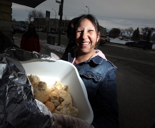 """Althea Guiboche hands out Bannock to passersby at Dufferin and Main Thursday afternoon. See her """"My Winnipeg"""" piece for Dave Conors. March 7, 2013 - (Phil Hossack / Winnipeg Free Press)"""