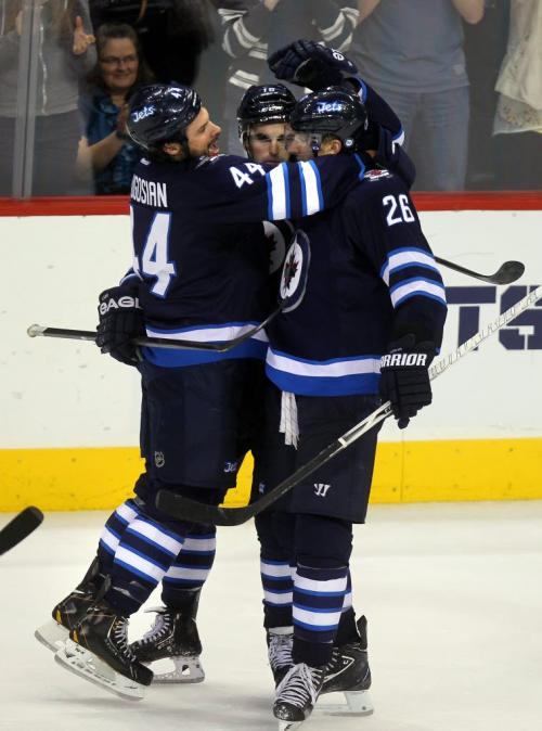 Left to right Winnipeg Jets Zach Bogosian, Andrew Ladd and Blake Wheeler celebrate Ladd's empty net goal late in 3rd period action at the MTS Center Thursday night. March 14, 2013 - (Phil Hossack / Winnipeg Free Press)