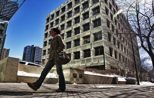 A pedestrian walks along Hargrave Street downtown past a building illuminated by the noonday sun reflecting off of the HSBC Bank Canada building.  130325 March 25, 2013 Mike Deal / Winnipeg Free Press