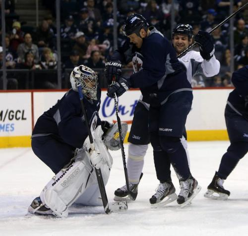 Winnipeg Jets' Olli Jokinen (12) and Mark Stuart (5) battle for position in front of goaltender Ondrej Pavelec (31) during practice at MTS Centre in front of about 3000 fans from the ticket waiting list who were invited to the special event, Sunday, April 14, 2013. (TREVOR HAGAN/WINNIPEG FREE PRESS)