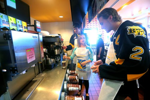 Brandon Sun Star FM's Carly Frey works behind the counter with Brandon Wheat Kings' Eric Roy and captain Ryan Pulock, right, during Wednesday's McHappy Days, in support of Westman Dreams for Kids, at the Richmond Avenue McDonald's restaurant. (Bruce Bumstead/Brandon Sun)