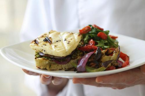 Grilled Haloumi cheese Sandwich. Haloumi cheese is grilled along with Foccacia Bread, red peppers and purple onion.  Pumpkin See spread in spread on bottom of sandwich along with grilled cheese and onion.  Sandwich is served with grilled red peppers and fresh greens topped with oven dried cherry tomatoes. Red River College Culinary Arts cooking course.  Photography by Ruth Bonneville Winnipeg Free Press June 15,, 2013