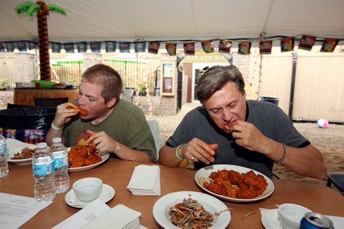 Brandon Sun 10082013 Danny Wilson and Frank McGuire work their way through as many hot wings as they can in seven minutes during the wing eating competition at the 1st Annual Margarita-Ville Beach Party at The Dock on Princess on Saturday afternoon. (Tim Smith/Brandon Sun)
