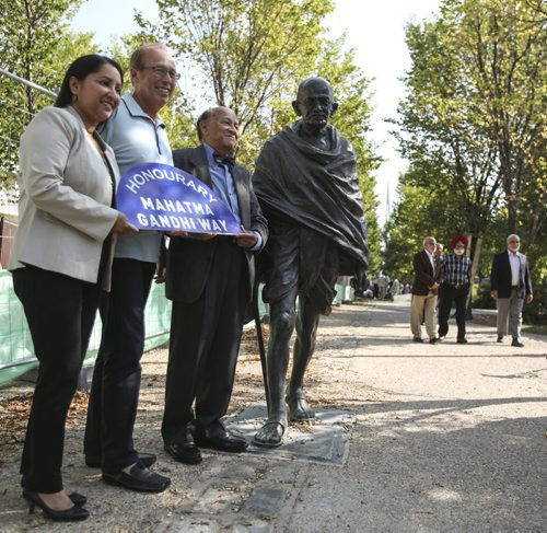 (Left to right) Councillor Devi Sharma, Mayor Sam Katz and Dr. K. Dakshinamurti (president of the Mahatma Gandhi Centre of Canada) stand with an effigy of Mahatma Gandhi near York St., which has been honourarily renamed Mahatma Gandhi Way between Main St. and Waterfront Dr. Thursday, August 15, 2013. (JESSICA BURTNICK/WINNIPEG FREE PRESS)