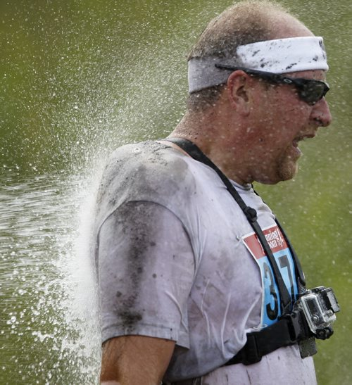 A participant is hosed off after completing the Dirty Donkey Run, a 5km run through a muddy obstacle course, at Springhill, Saturday, August 17, 2013. (TREVOR HAGAN/WINNIPEG FREE PRESS)