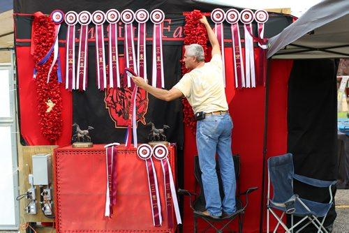 Brandon Sun 17082013 Steve Wakeman with Imagine Farms in Kansas hangs the National Champion Stock Hunter Halter Mare class award alongside other awards won by Imagine Farms during the Arabian & Half-Arabian Championship Horse Show at the Keystone Centre on Saturday.  (Tim Smith/Brandon Sun)