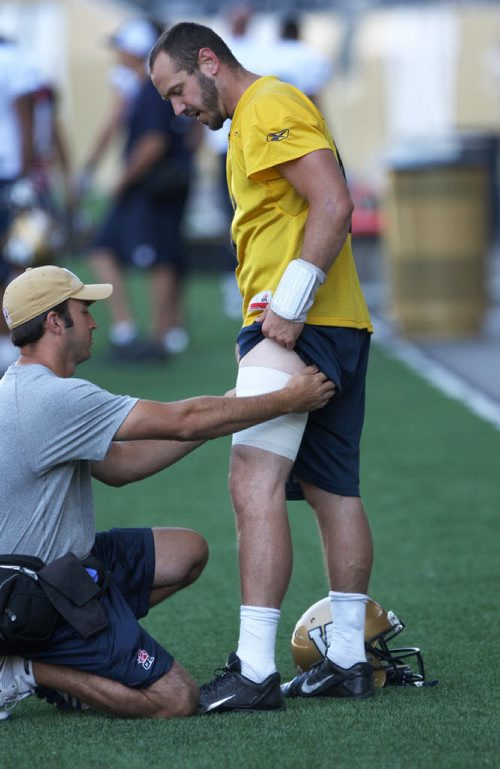 Winnipeg Blue Bombers quarterback Buck Pierce gets a tensor bandage applied by head athletic therapist Alain Couture on the field during practice Thursday at Investors Group Field -See story- August 22, 2013   (JOE BRYKSA / WINNIPEG FREE PRESS)